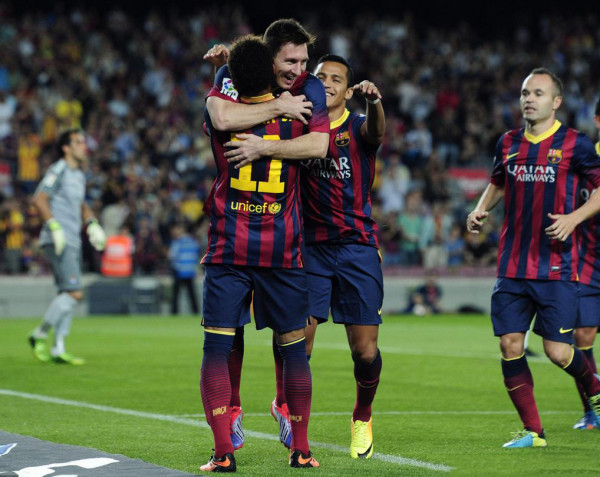 Lionel Messi jumping in Neymar's direction, to hug him and thank him for the assist