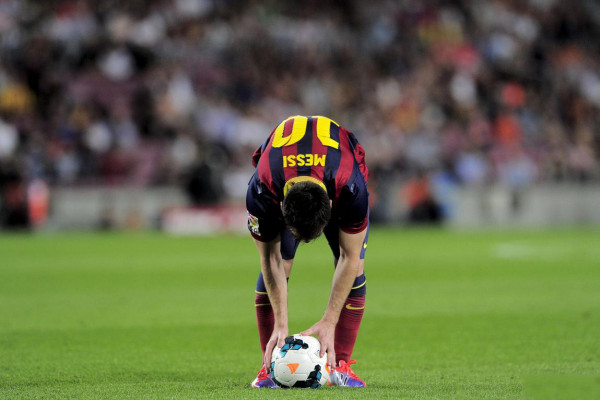 Lionel Messi bends down before taking a free-kick for Barcelona