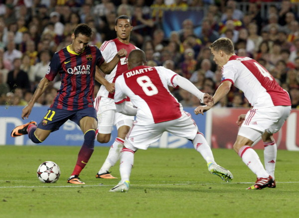 Neymar trying to shoot the ball between the legs of two Ajax defenders