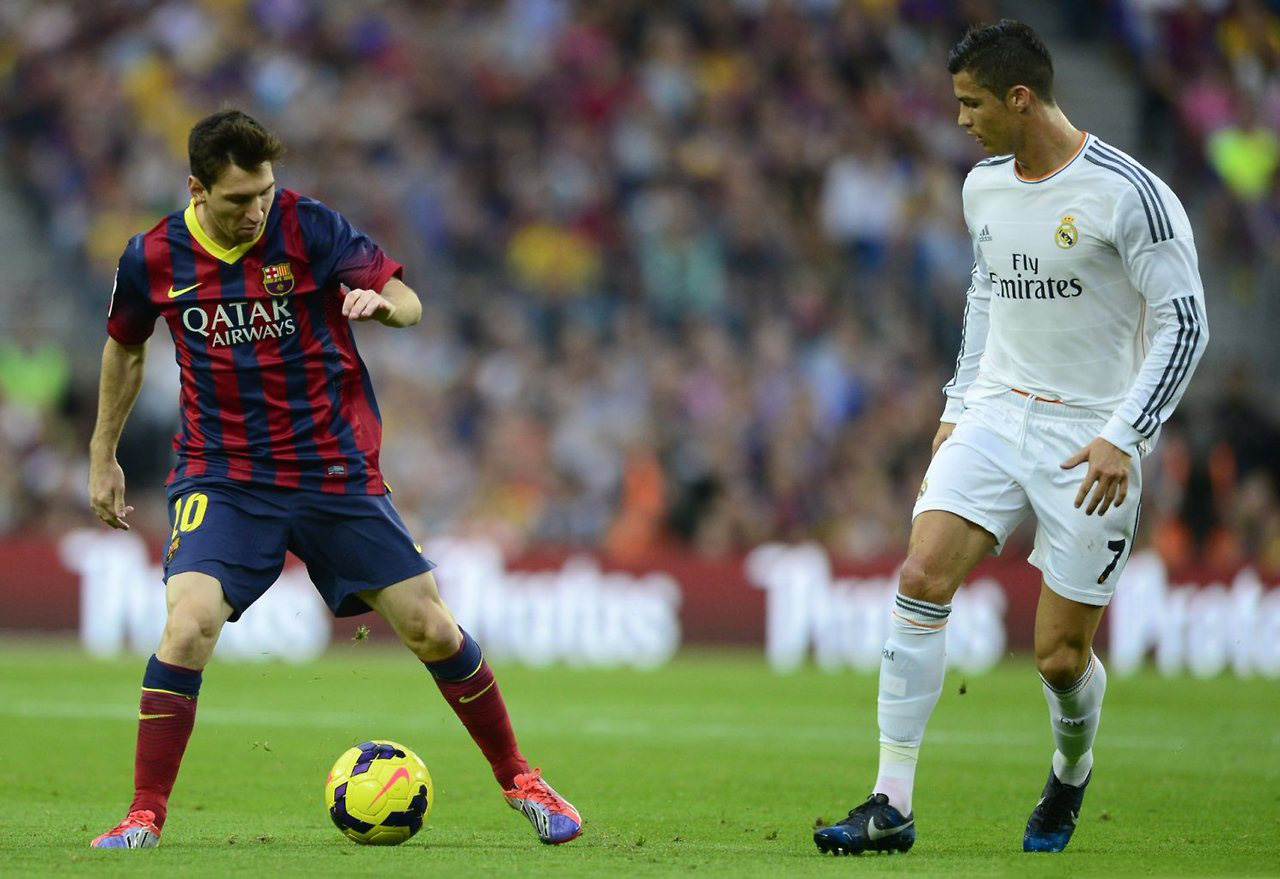 Lionel Messi holding to the ball, with Cristiano Ronaldo observing