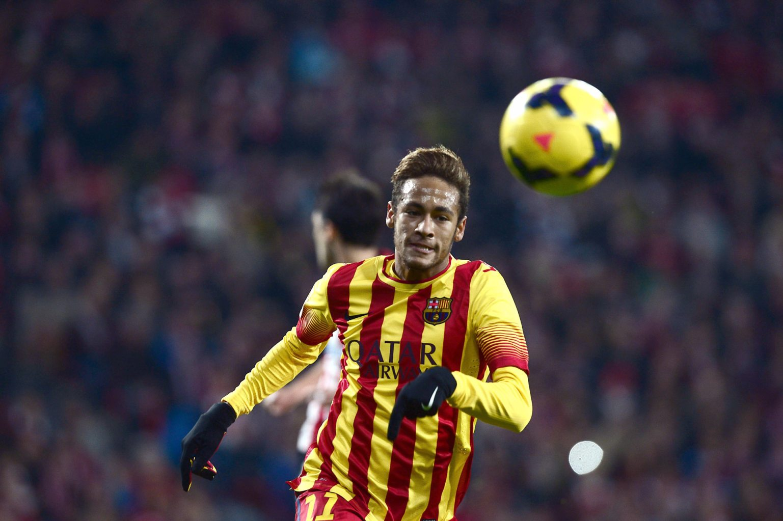 Neymar chasing the ball in a Barcelona red and yellow stripes jersey
