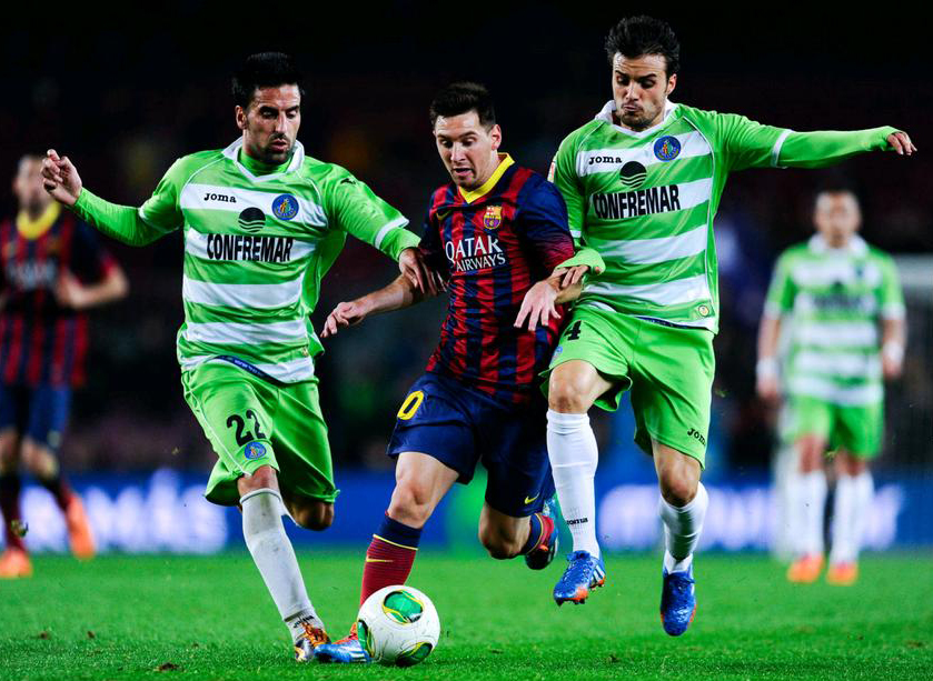 Lionel Messi dribbling between two defenders at the same time