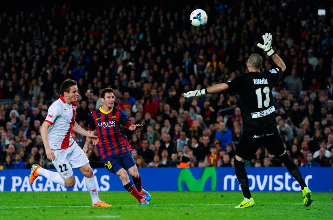 Lionel Messi chipping the ball above the goalkeeper's head