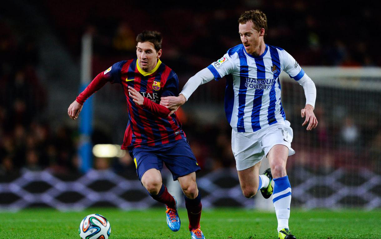 Lionel Messi running away from a Real Sociedad defender