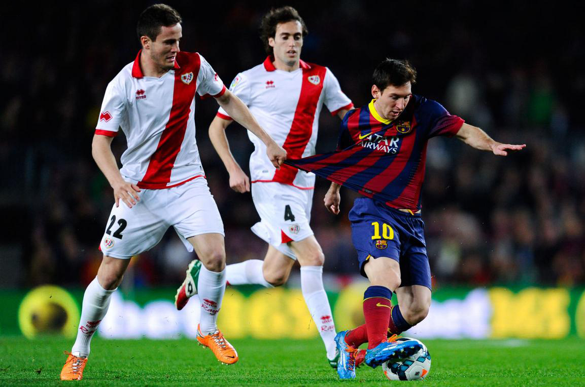 Messi being hold by his shirt, as he gets past a defender
