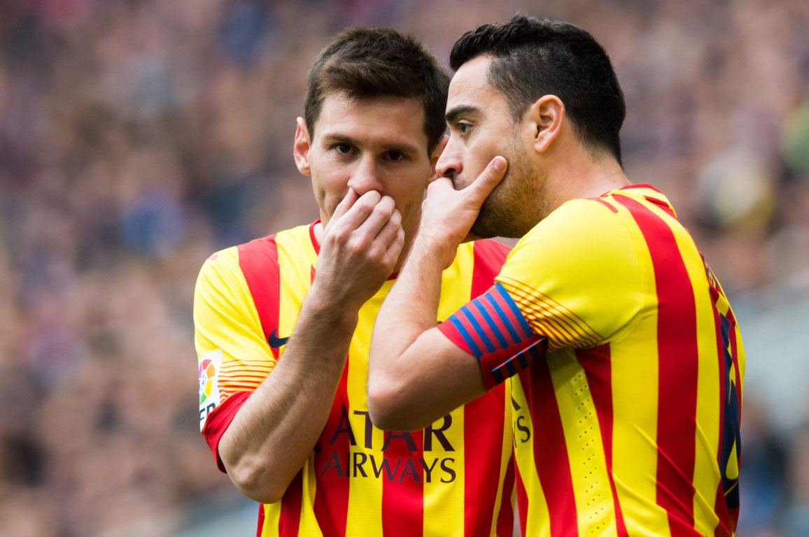Lionel Messi whispering a secret to Xavi
