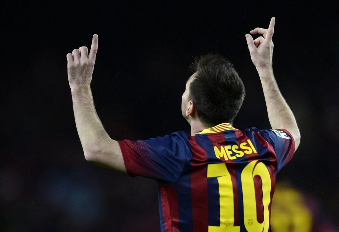 Messi pointing his two fingers to the sky, after scoring a goal for Barcelona