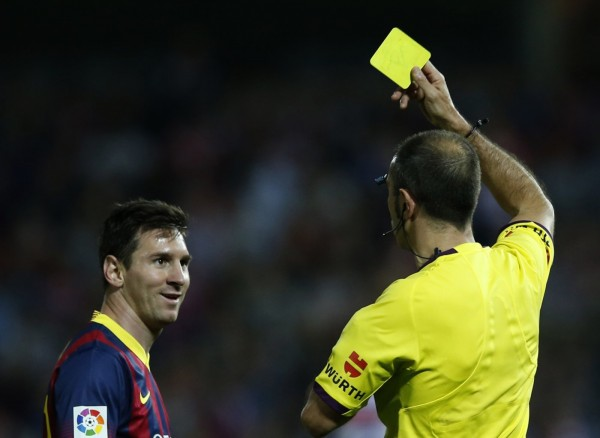 Messi being shown the yellow card and reacting with a smile