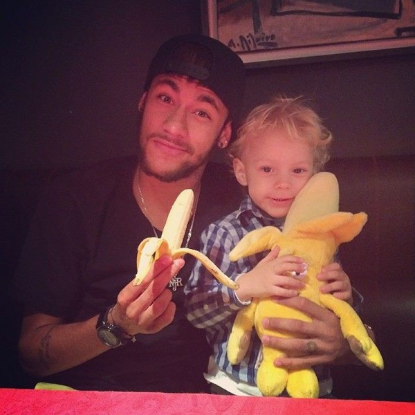 Neymar and his son David Luccas eating a banana in a campaign against Racism