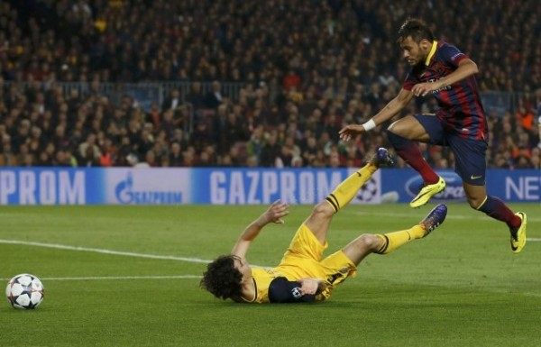 Neymar jumping over a defender, during a Barcelona vs Atletico Madrid game