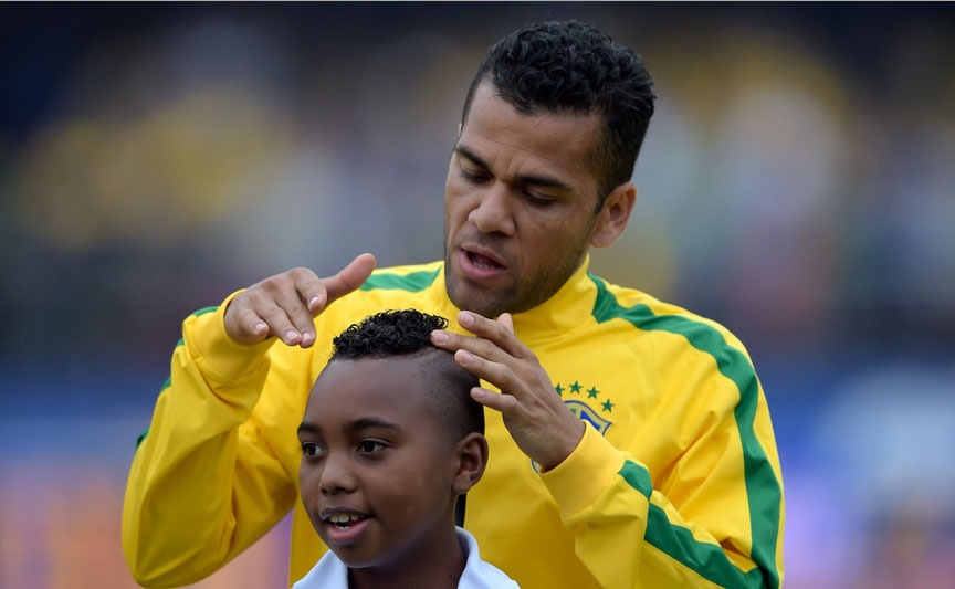 Daniel Alves combing a little kid's hair