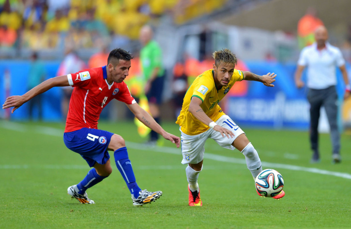 Neymar racing past a defender against Chile, in the FIFA World Cup 2014