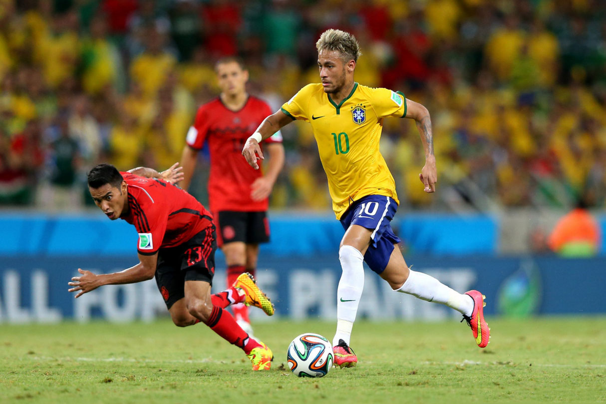 Neymar skipping past a defender in Brazil vs Mexico for the FIFA World Cup 2014