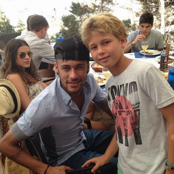 Neymar posing for a photo with a young fan
