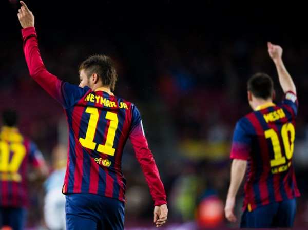 Neymar and Messi raising their hands up in the air