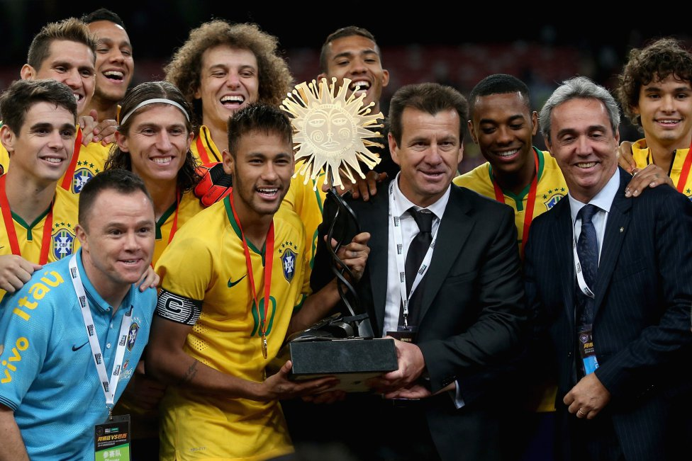 Neymar holding a trophy next to Dunga