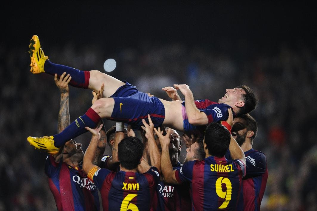 Lionel Messi being thrown to the air by his Barcelona teammates