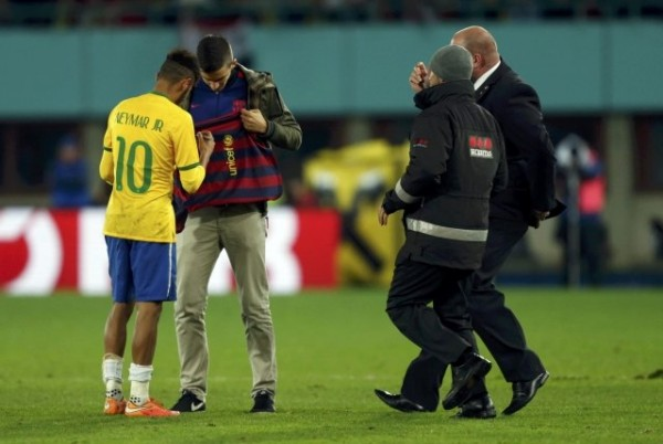 Neymar signing an autograph to a pitch invader in Austria vs Brazil